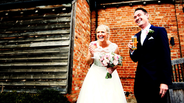 Bride and groom celebrating their wedding at Bassmead Manor Barns in St neots