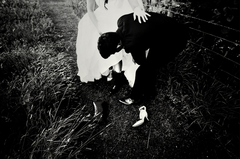 Black and white photograph of a bride putting wellies on