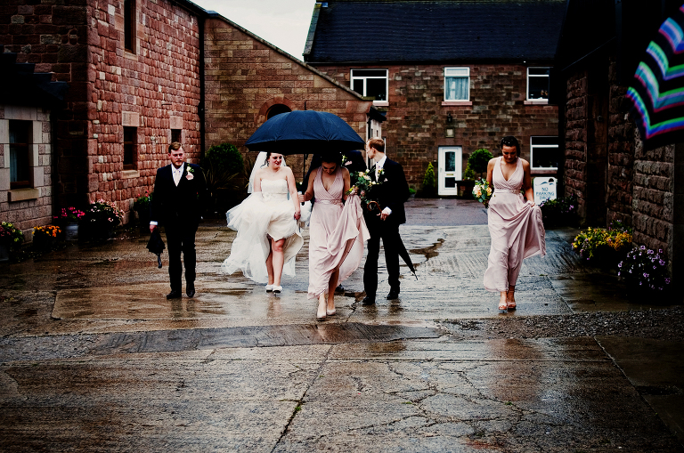 Bride and groom with brollies on the rainy wedding day
