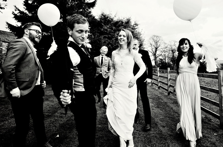 A black and white photograph of the bride and groom with bridal party at The Shireburn Arms