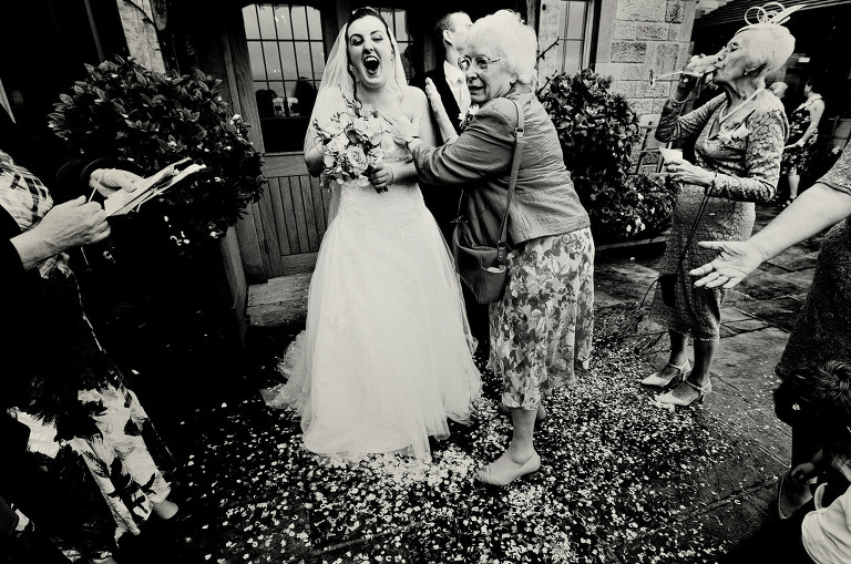 Bride and grandmother laughing after confetti throw at Heaton House Farm wedding